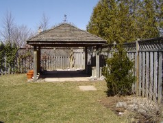 Large fenced rear yard with covered gazebo.