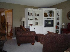 Spacious family room has an attractive berber carpet, cathedral ceiling and a wonderful custom built bookcase with TV center.