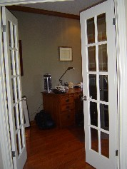 Double french doors leading to main floor den located near the front of the house